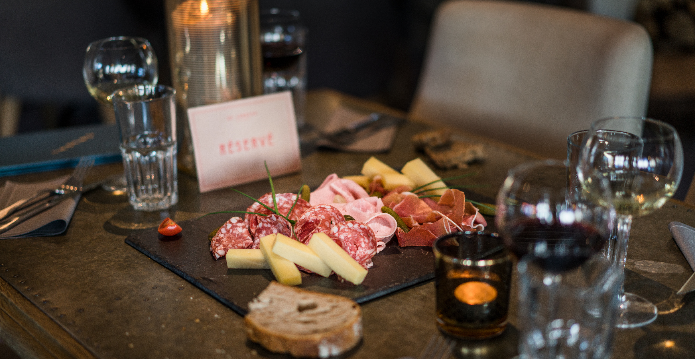 Charcuterie and cheese board with De Laroche branded reserved sign table setting