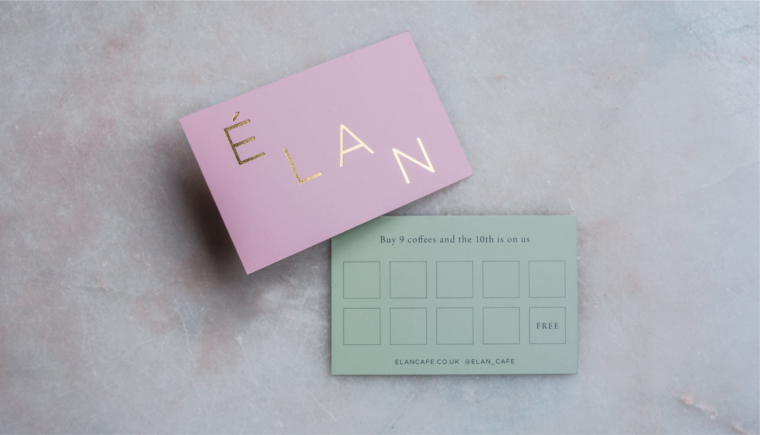 Graphic design of Elan Café loyalty card. Gold foil logo on pink and green card shot on marble background
